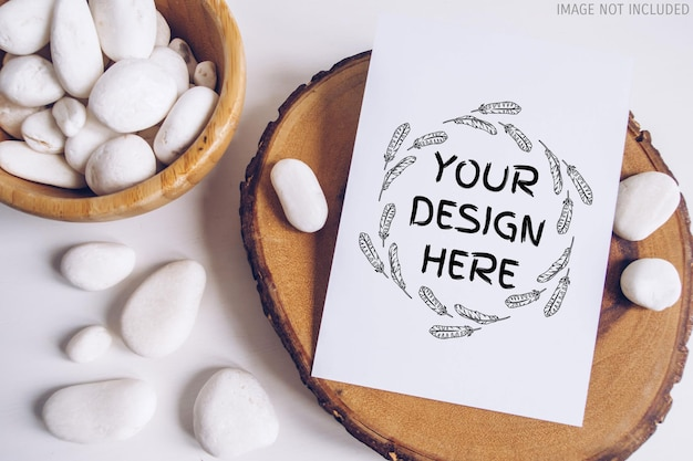 Boho vertical postcard mockup with white pebble and wooden cut section on white table background. rustic bohemian image. space for text. copyspace mock up