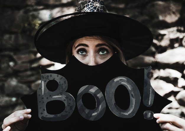 Boo! sign with woman dressed as a witch