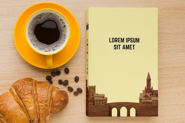 Book cover composition on wooden background with cup of coffee