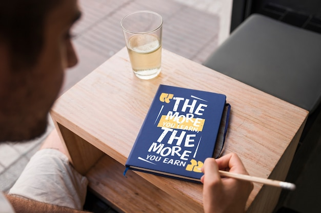 Book cover mockup in front of young man