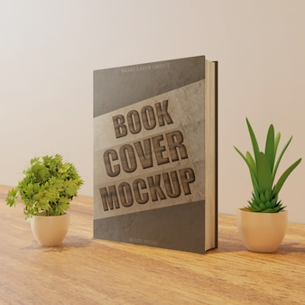 Book cover mockup on wooden table with couple plants