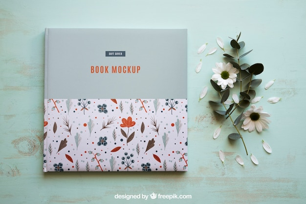 Book mockup next to flowers
