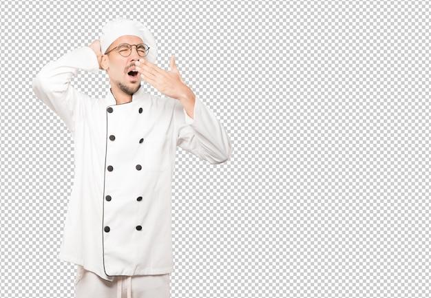 Скучающий молодой шеф-повар зевая жест