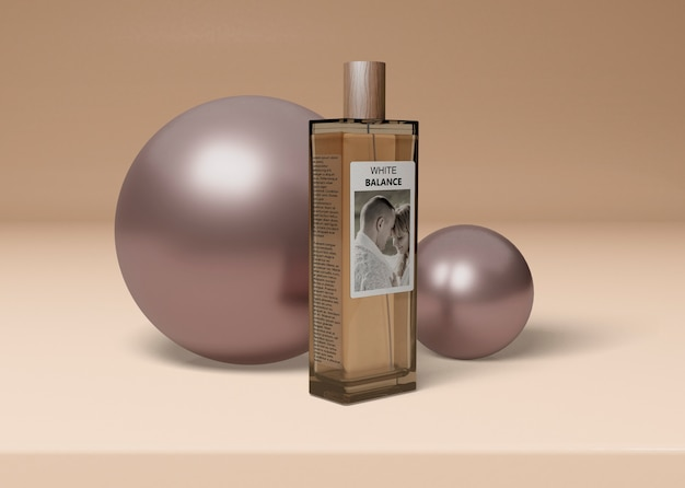Bottle of perfume beside balls