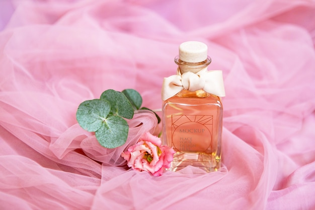 Bottle of perfume with flowers on pink textile surface