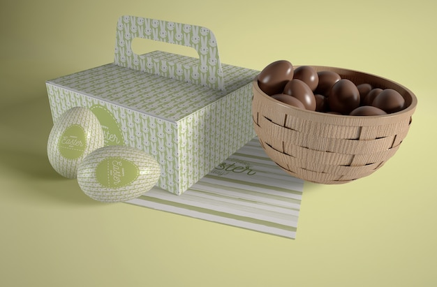 Box and bowl with easter eggs on table
