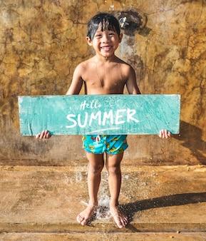 Boy holding a hello summer board