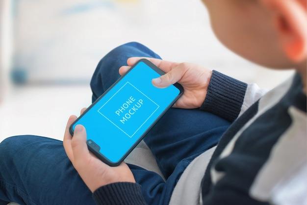 少年は、スマートフォンのコンセプトでゲームをプレイします。アプリ、ゲームプレゼンテーションモックアップのスマートオブジェクト画面。
