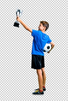 Boy playing soccer and holding a trophy