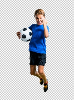 Boy playing soccer and jumping