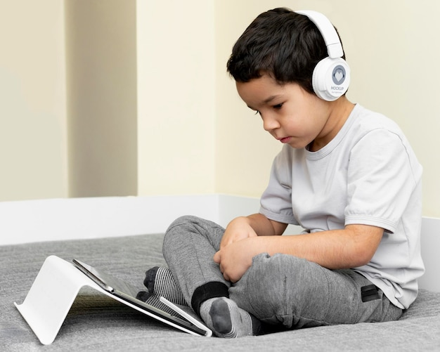 Boy with headphones using tablet