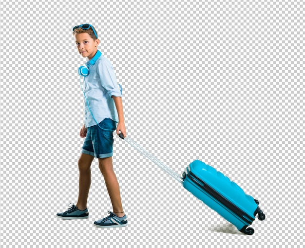 Boy with sunglasses and headphones traveling with his suitcase