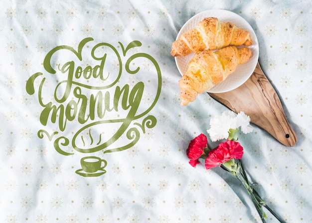 Breakfast in bed with croissants and flowers