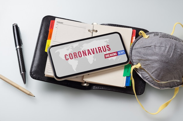 Последние новости, мобильный телефон covid-19 mockup с лицевыми масками на офисном столе Premium Psd