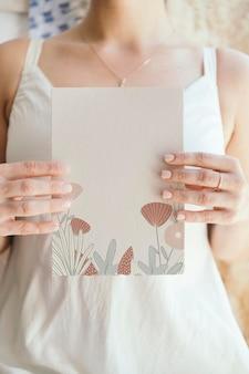 空白の白いカードのモックアップを保持している花嫁