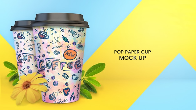 Bright and colorful paper cup mockup of two paper coffee cups with plants, foliage, and yellow flowers