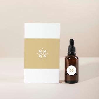 흰색 상자 제품이 있는 갈색 유리 스포이드 병