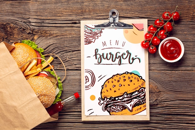 Бургер меню в бумажном пакете на деревянном фоне