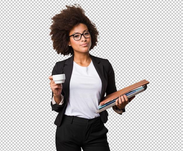 コーヒーとファイルのカップを保持しているビジネス黒人女性