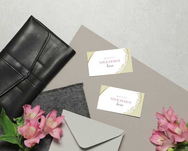 Business card on grey background with flowers, envelope and purse