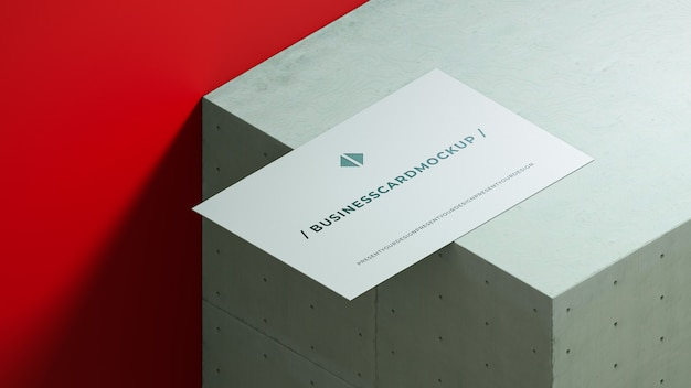 Business card mockup on concrete square with red background.