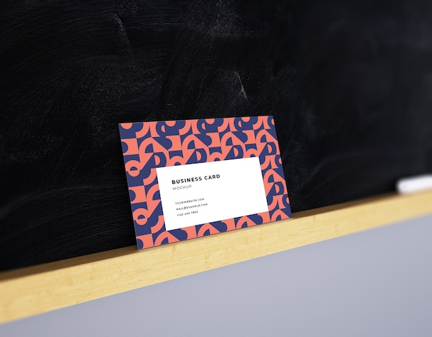 Business card mockup on dark blackboard background with wood shelf and chalk