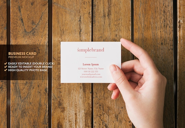 Business card mockup held by a hand on a wooden table