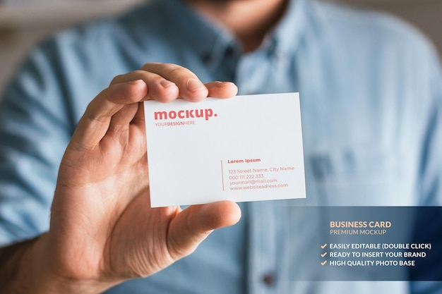Business card mockup held by a man in hand