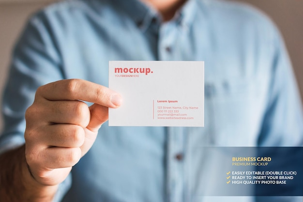 Business card mockup held by a man's hand