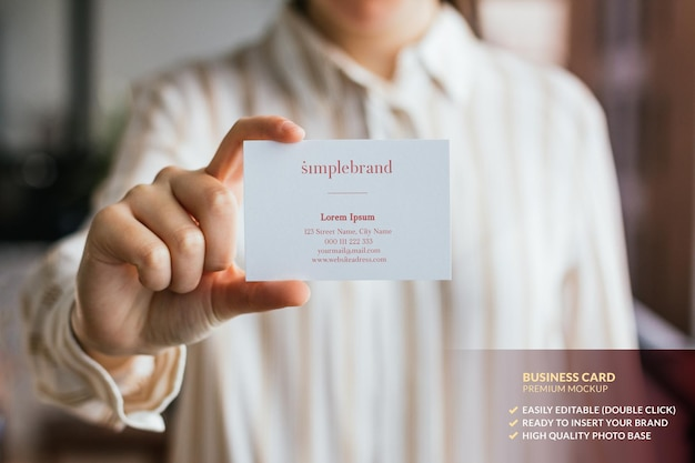 Business card mockup held by a woman's hand