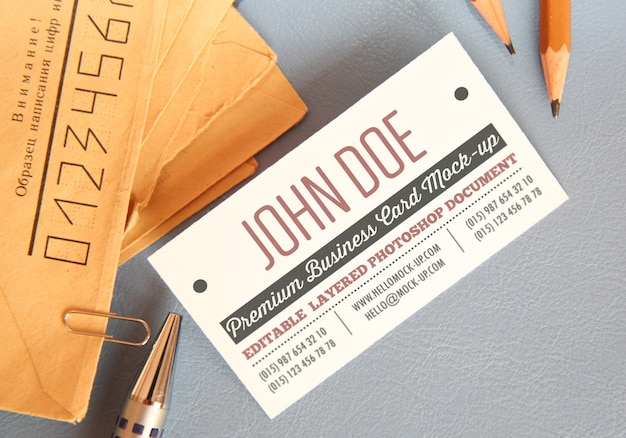 Business card mockup template with envelops on background with pencils