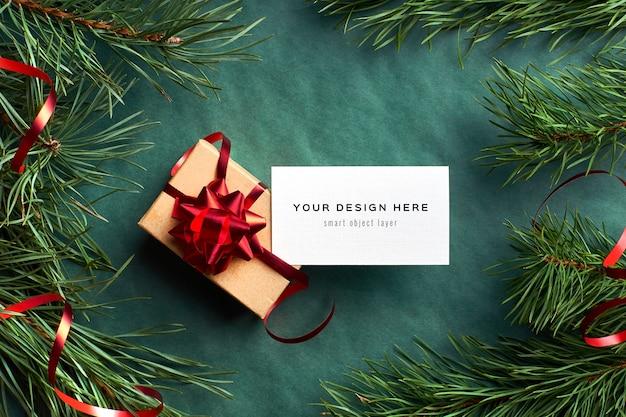 クリスマスギフトボックスと緑の松の木の枝と名刺のモックアップ