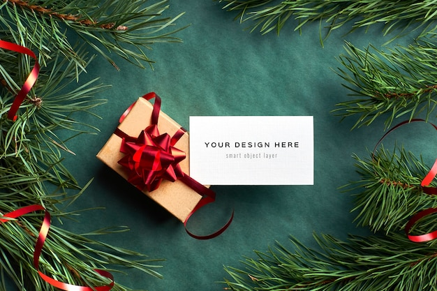 Business card mockup with christmas gift box and pine tree branches on green