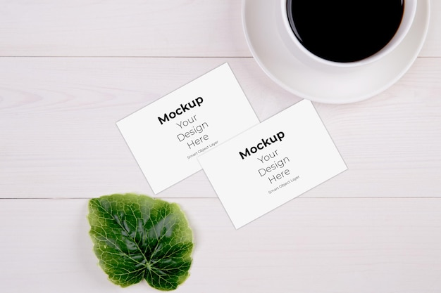 Business card mockup with leaf and cup of coffee on wooden table
