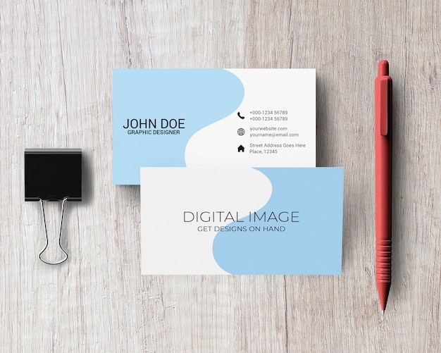 Business card mockup with pen and binder clip