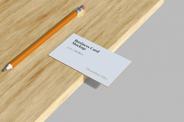 Business card mockup with pencil on the wood