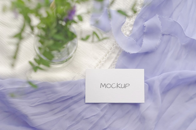 Business card mockup with violet flowers and delicate silk ribbons on a white space