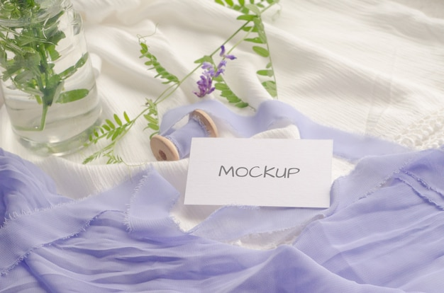 Business card mockup with violet flowers and delicate silk ribbons on white