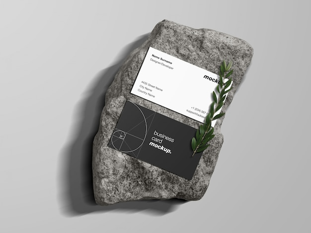 Business cards on a rock with green branch mockup template