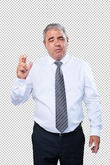 Business man doing a luck gesture