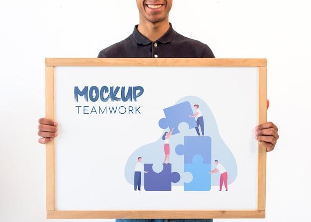 チームワークのモックアップを保持しているビジネスマン
