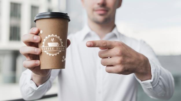 Деловой человек, указывая на макет кофейной чашки
