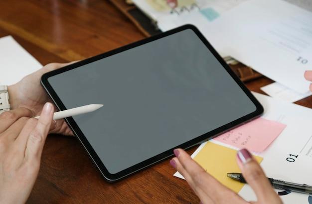 회의에서 디지털 태블릿 모형과 함께 무선 스타일러스를 사용하는 비즈니스 사람