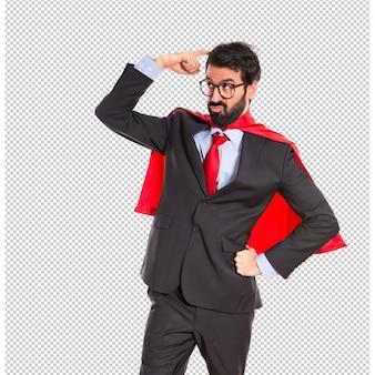 Businessman dressed like superhero thinking over white