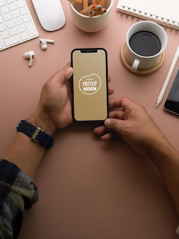 スマートフォンのモックアップを使用してビジネスマンの手