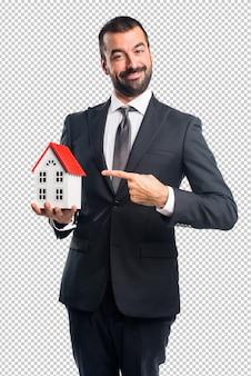 Businessman holding a little house