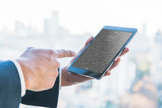 Businessman with finger at tablet in front of city skyline