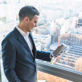 Businessman with tablet in front of city skyline