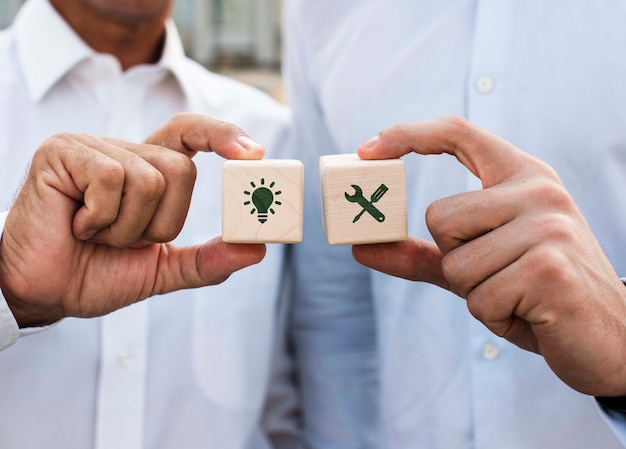 Businessmen holding dices with company ideas front view