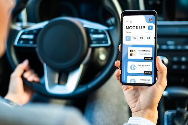 Imprenditrice in auto tenendo il telefono mockup